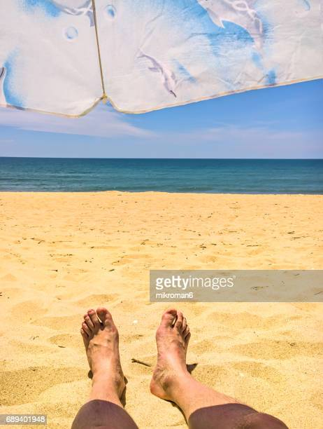 a man laying in faro beach on hot summer day. - faro city portugal stock photos and pictures