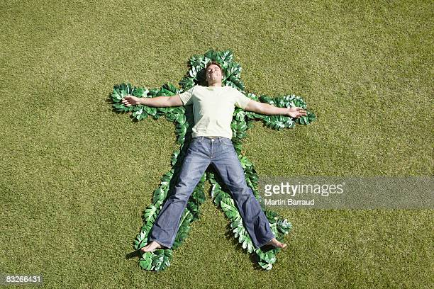 Man laying in grass outlined by green leaves