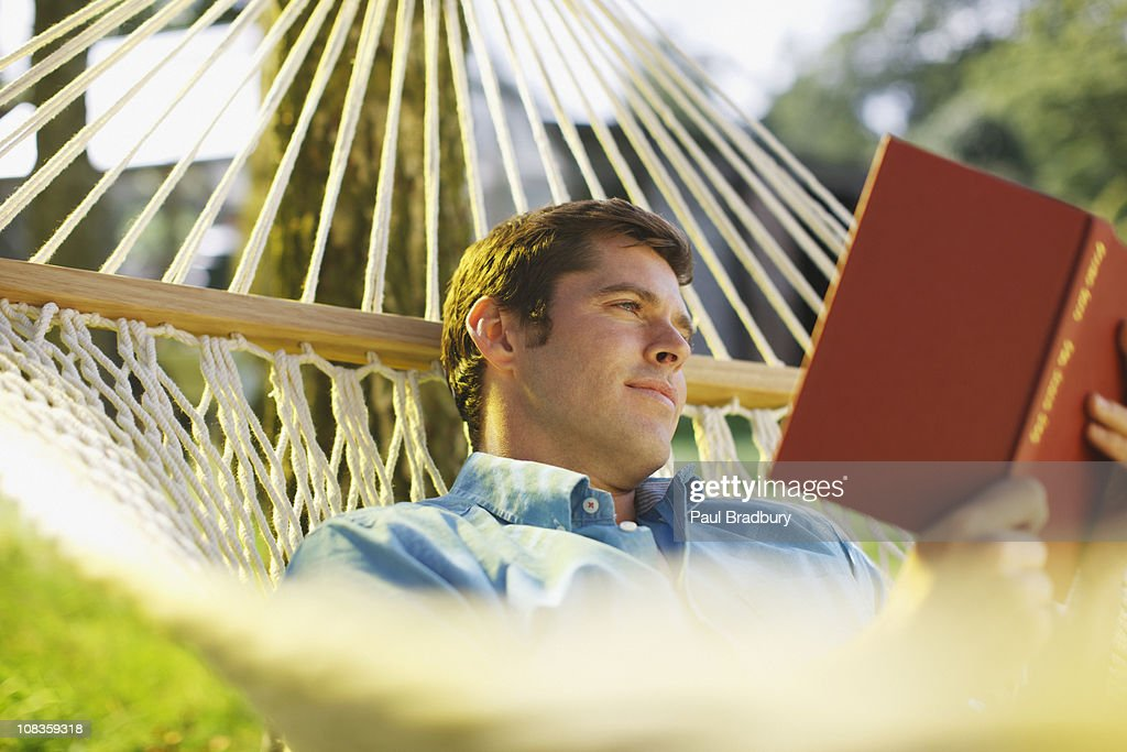 Man laying in hammock reading book : Stock Photo