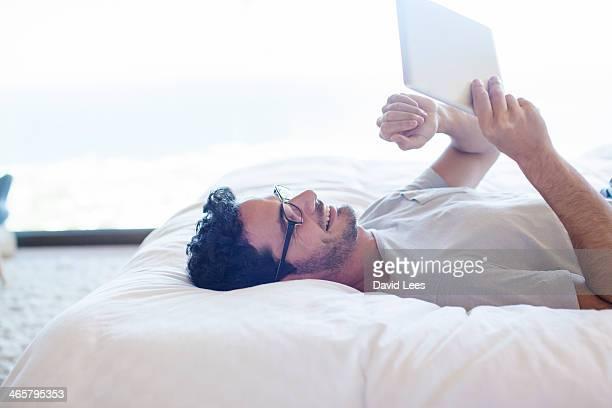 Man laying on bed using digital tablet