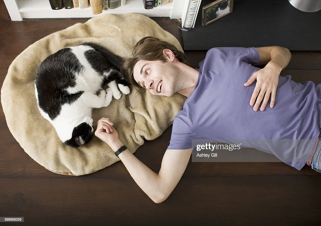 Man laying on floor with cat : Stock Photo