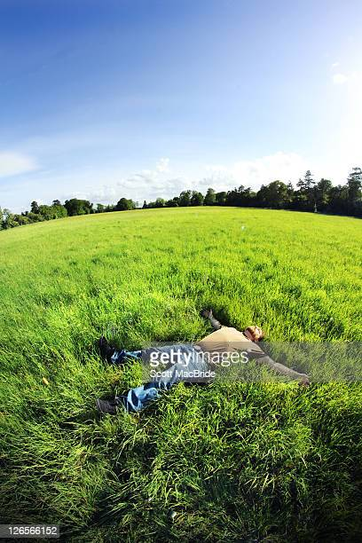 man laying on grass - scott macbride stock pictures, royalty-free photos & images
