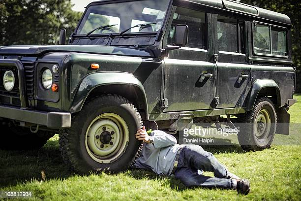 Man laying on grass repairing off road vehicle.