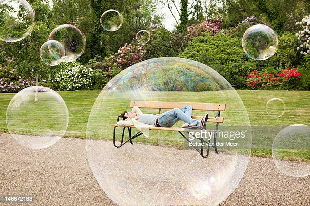man laying on park bench, surrounded by bubbles.