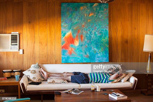 man laying on sofa - laziness stock pictures, royalty-free photos & images