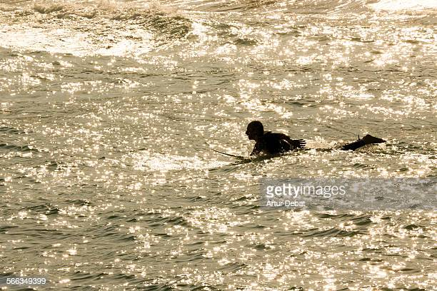 Man laying on surf board rowing with hands and the sun reflected on the Mediterranean Sea in the Barcelona shoreline Vilassar de Mar Catalonia Europe...