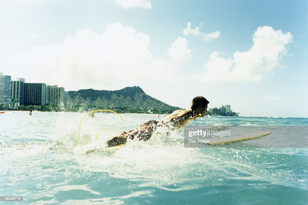 Man laying on surfboard paddling with hands in water : Stock Photo