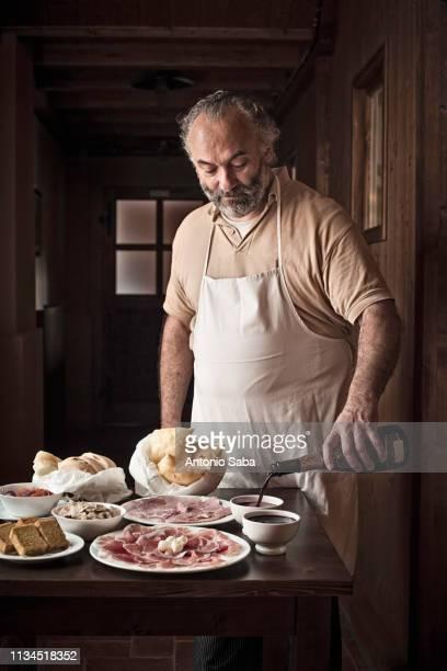 man laying out meat, bread and sauce - cultura italiana fotografías e imágenes de stock