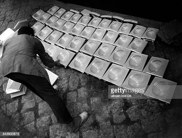 Man laying out stove tiles on the floor Photographer Ullmann Published by 'Hier Berlin' 14/1936Vintage property of ullstein bild