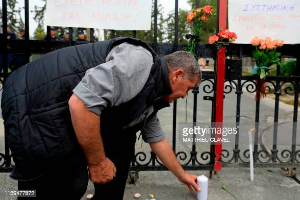 A man lays a candle as protesters demonstrate in support of the victims of a suspected serial killer in front of the presidential palace in Nicosia...