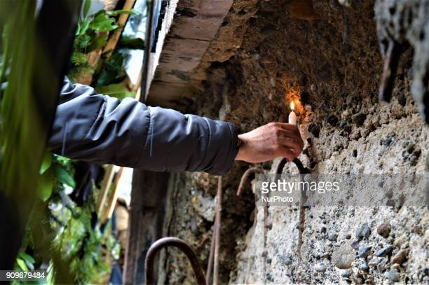 A man lays a candle next to the wall of a monument as people gather on the spot where Turkish journalist Ugur Mumcu was assassinated during a...