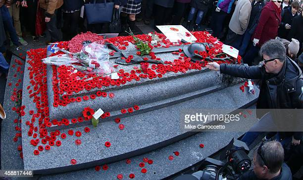 A man lays a poppy on the Tomb of the Unknown Soldier after this morning's Remembrance Day ceremony November 11 2014 in Ottawa Canada An estimated...