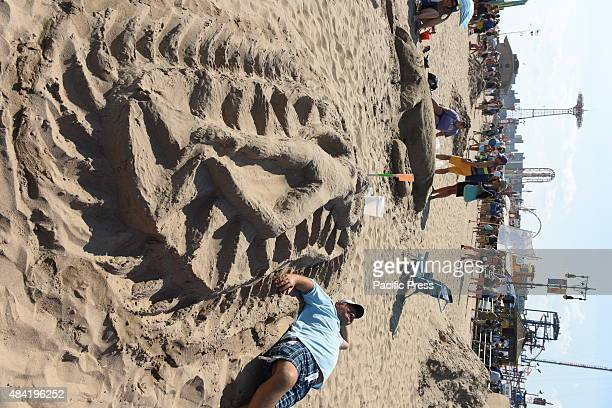 Man lays alongside a sculpture of a nude sunbather. Contestants and teams participated in the 25th annual Coney Island Sand Sculpting contest.