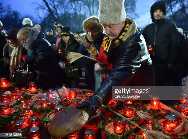 A man lays black bread and lit candles during a commemoration ceremony at a monument to victims of the Holodomor famine of 193233 in Kiev on November...