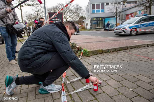 Man lays candles and flowers in front of one of the bar target in a shooting in Kesselstadt, near Frankfurt, western Germany, on February 20, 2020. -...