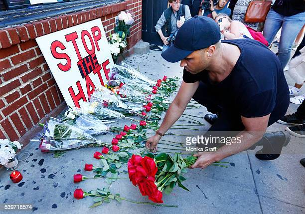 A man lays down 50 roses to honor each victim of the gay Orlando night club shooting as people gather outside of the Stonewall Inn as a vigil is held...