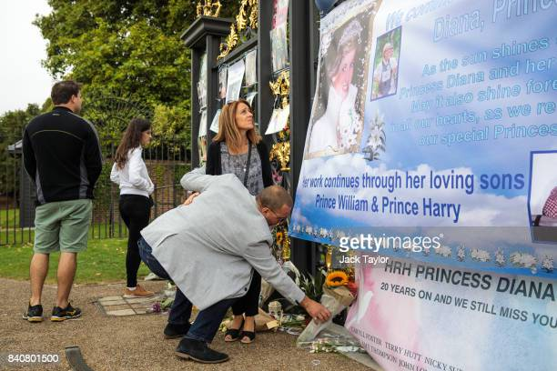 A man lays floral tributes outside an entrance gate to Kensington Palace ahead of the 20th anniversary of the death of Diana Princess of Wales on...