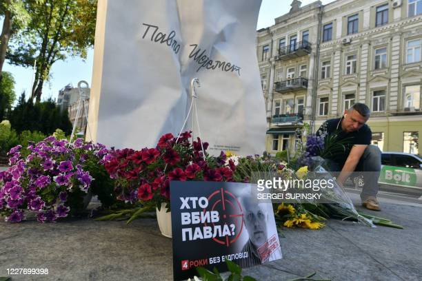 Man lays flowers at a memorial to journalist Pavel Sheremet on the site where Sheremet's car exploded on the 4th anniversary of his death in Kiev on...