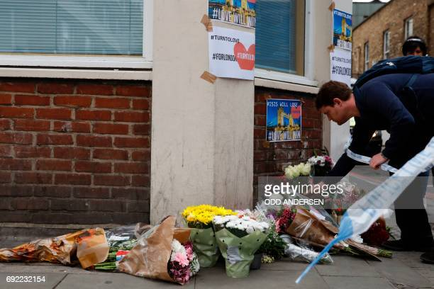 A man lays flowers at a police cordon on Borough High Street south of Borough Market below posters regarding the May 22 Manchester terror attack in...