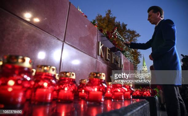 A man lays flowers at the WWII Hero Cities Memorial to the city of Kerch in downtown Moscow on October 17 after nineteen people were killed and...