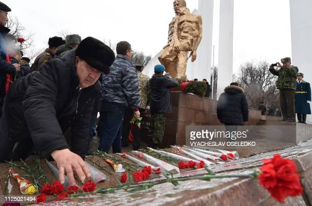 A man lays flowers during a commemorative ceremony at a memorial monument to the Soviet soldiers killed in Afghanistan while fighting against the...