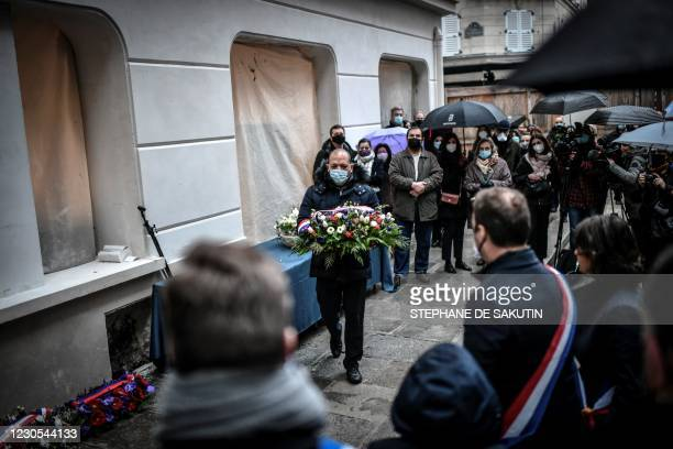 Man lays flowers during a commemorative ceremony on January 12, 2021 in Paris to mark two years since a powerful gas explosion tore through a...