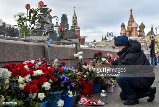 A man lays flowers in central Moscow on February 25 2018 at the site where late opposition leader Boris Nemtsov was fatally shot on a bridge near the...