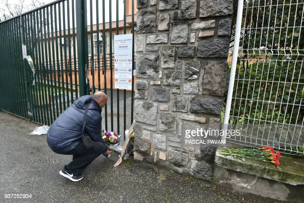 A man lays flowers in front of the Gendarmerie Nationale in Carcassonne on March 24 2018 in tribute to the gendarme killed after swapping himself for...