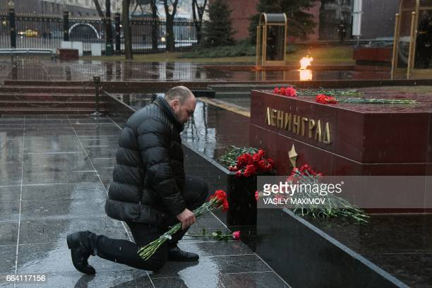 TOPSHOT A man lays flowers in memory of victims of the blast in the Saint Petersburg metro at a memorial stone reading Leningrad by the Kremlin wall...