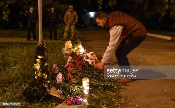 A man lays flowers near a college in Kerch Crimea on October 17 after a student opened fire at a technical college in the Russianannexed Crimea city...