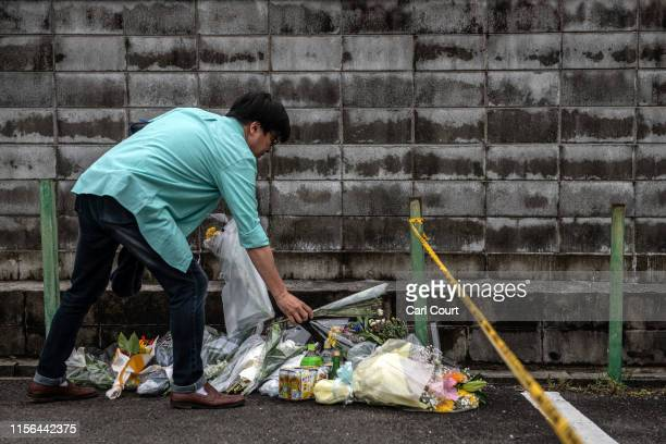 Man lays flowers near the Kyoto Animation Co studio building after an arson attack, on July 19, 2019 in Kyoto, Japan. Thirty three people are...