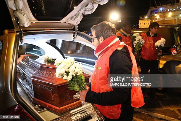 A man lays flowers on the coffins of immigrants who died trying to reach the Italian coast arrive from Lampedusa on February 11 2015 in Porto...
