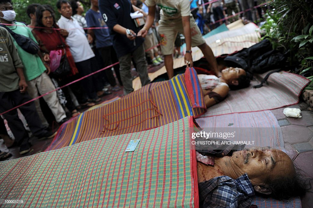 A man lays identity cards over the the dead bodies of anti-government protesters killed in a gunbattle the day before at a temple which had been turned into a shelter within an anti-government protest site in downtown Bangkok on May 20, 2010. Gunshots rang out near a Buddhist temple in the heart of an anti-government protest zone in Bangkok, and soldiers were advancing on foot along an elevated train track, an AFP photographer saw. Thai security forces stormed the 'Red Shirts' protest camp on May 19 in a bloody assault that forced the surrender of the movement's leaders who asked their supporters to disperse. AFP PHOTO/Christophe ARCHAMBAULT