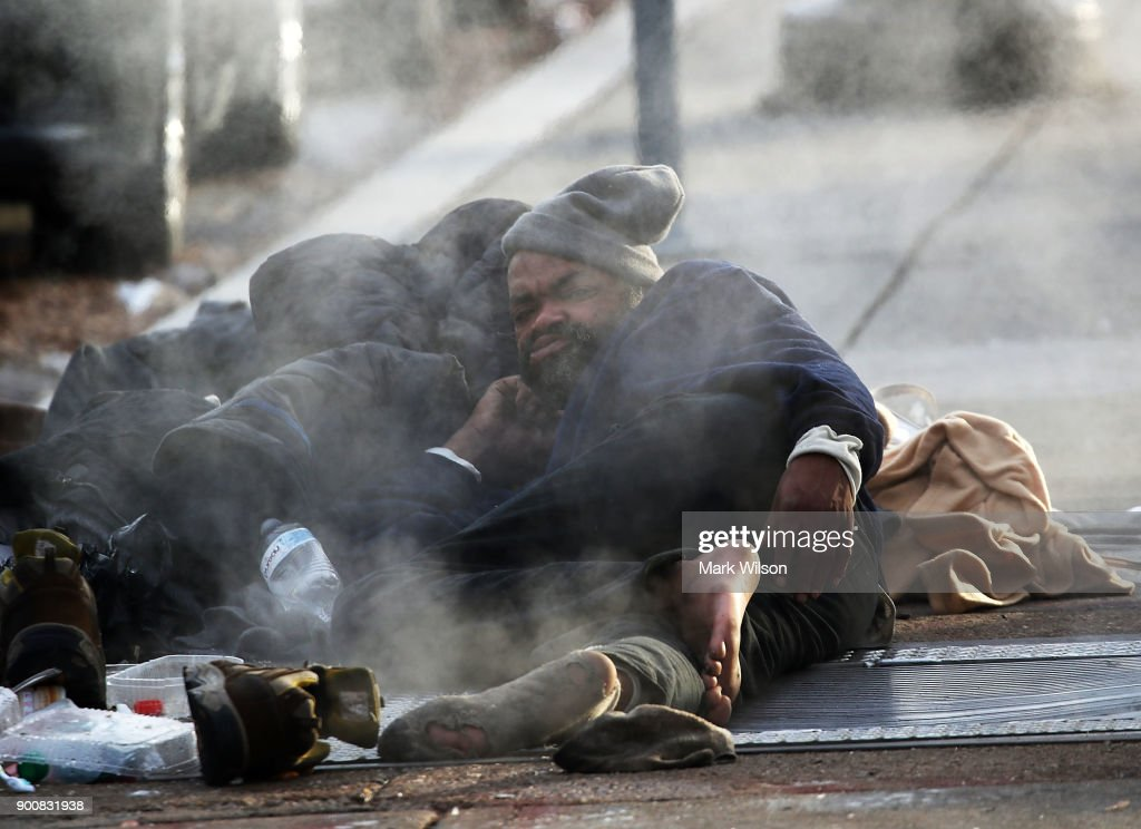 A man lays on a warm steam grate on January 3, 2018 in Washington, DC. A winter storm is traveling up the east coast overnight with significant accumulationsÊof snow possible.