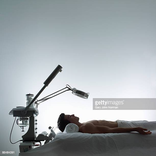 Man lays on table with microdermabrasion machines
