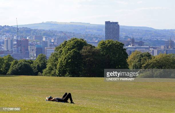 Man lays on the grass to enjoy the sunshine in Norton park in Sheffield, northern England on May 14 following an easing of the novel coronavirus...
