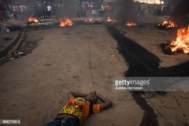 A man lays on the ground in front of a burning roadblock lit in protest for opposition presidential candidate Raila Odinga in the Kibera slum on...