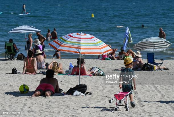 Man lays on the sand under a parasol as a boy walks with a stroller on the beach in Palavas-les-Flots, southern France, on June 10 during a heat wave...