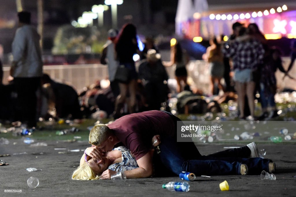 A man lays on top of a woman as others flee the Route 91 Harvest country music festival grounds after a active shooter was reported on October 1, 2017 in Las Vegas, Nevada. A gunman has opened fire on a music festival in Las Vegas, leaving at least 2 people dead. Police have confirmed that one suspect has been shot. The investigation is ongoing. The photographer witnessed the man help the woman up and they walked away. Injuries are unknown.