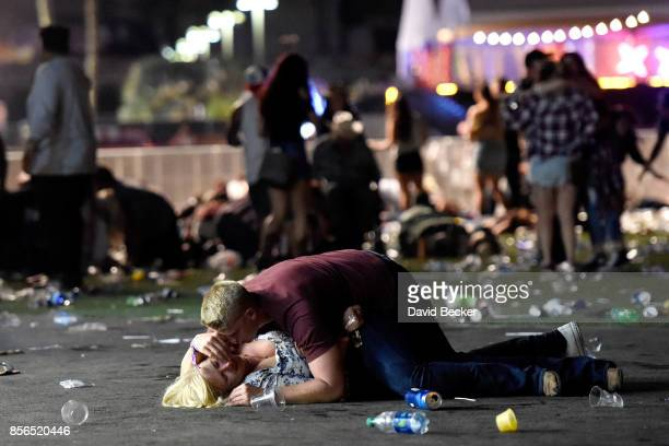 A man lays on top of a woman as others flee the Route 91 Harvest country music festival grounds after a active shooter was reported on October 1 2017...