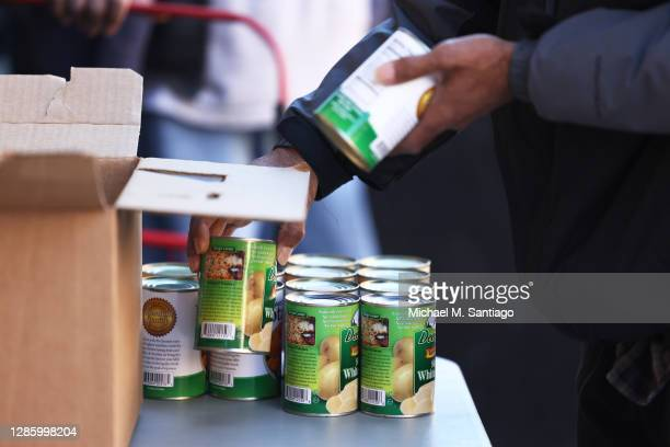 Man lays out canned food on a table during a Thanksgiving food distribution event at Food Bank For New York City in the Harlem neighborhood on...