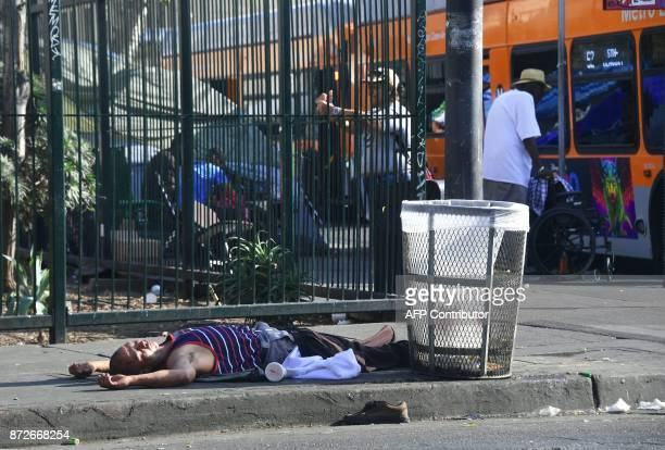 A man lays passed out beside a garbage can on the street on November 10 2017 in Los Angeles California home to one of the nation's largest homeless...
