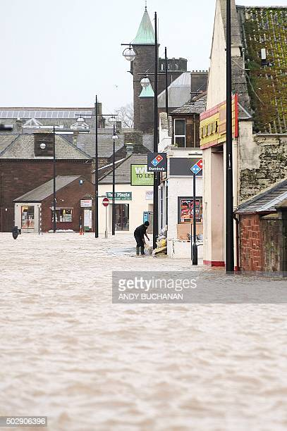 Man lays sandbags at the door of a shop in a flooded area along the River Nith, which burst its banks, in Dumfries, southern Scotland, on December...