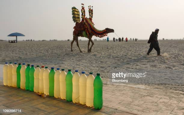 A man leading a camel past bottles filled with water for washing feet at Clifton Beach in Karachi Pakistan on Sunday Dec 23 2018 Women and children...