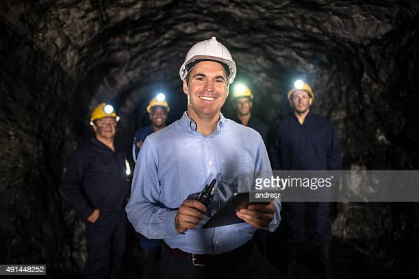 Man leading a group of men working at a mine