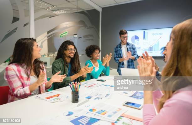 Man führt ein Treffen in einem Konferenzraum und applaudieren jemand für ihre monatlichen Verkäufe