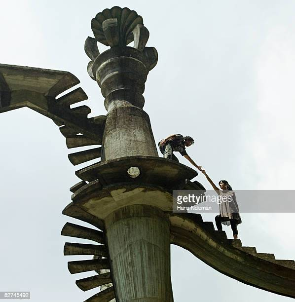 man leading a woman up a surreal structure - las posas stock pictures, royalty-free photos & images