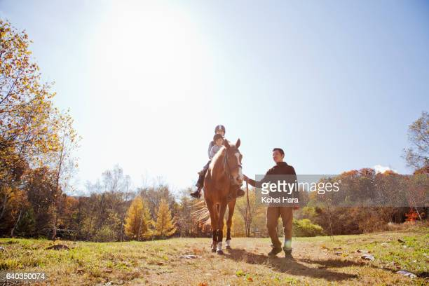 Man leading mother and son who are riding on horse in pasture