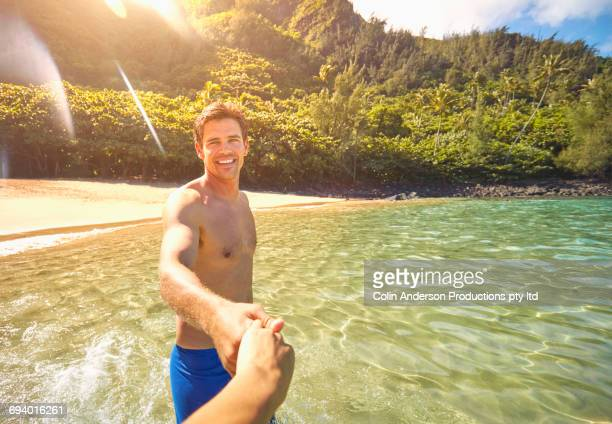 Man leading woman into ocean