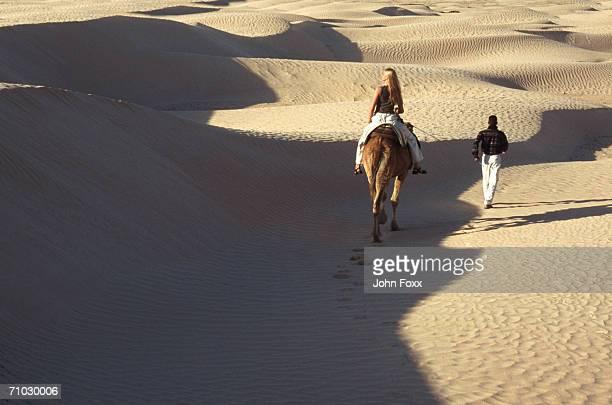 Man leading woman on horse in desert, rear view